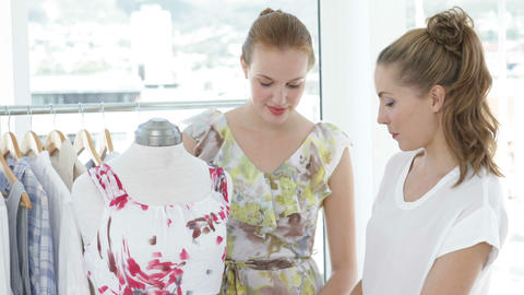 Two friends admiring a dress on a mannequin Stock Video Footage