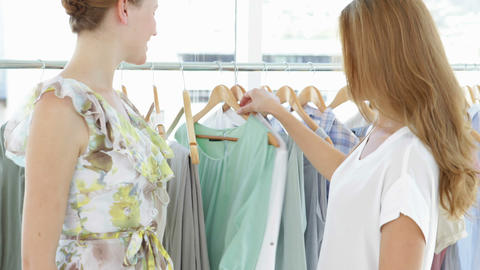 Two pretty friends looking through clothes rails Stock Video Footage