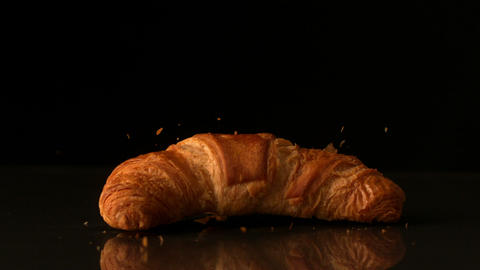 Croissant falling onto black surface Stock Video Footage