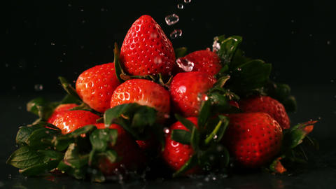 Water drops on strawberries on black surface Footage