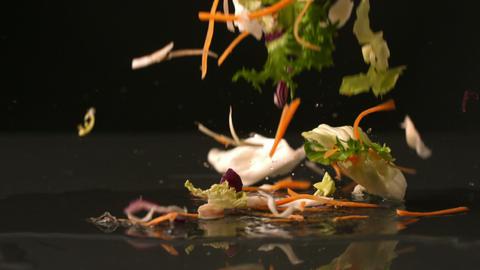 Salad falling onto black surface Stock Video Footage