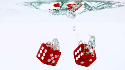 Two red dice falling in water Stock Video Footage