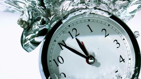 Alarm clock falling into water Footage