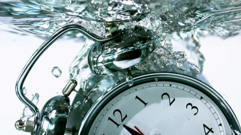 Alarm clock falling into water Stock Video Footage