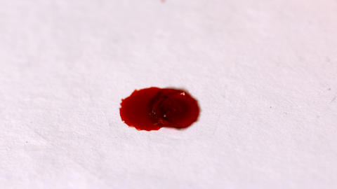 Blood dropping on white surface Footage