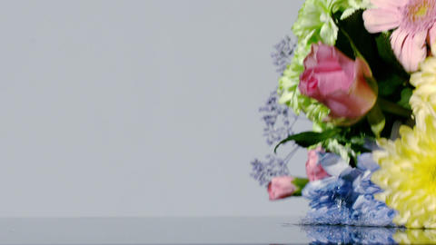 Bouquet of colourful flowers falling onto wet surface Footage