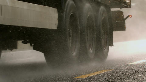 Heavy lorry driving over wet road Stock Video Footage