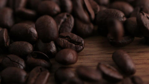 Coffee beans pouring onto wooden surface Stock Video Footage