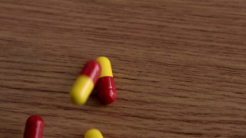 Pills falling onto wooden table Stock Video Footage