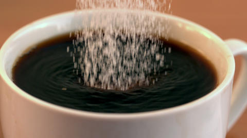 Sugar pouring into cup of coffee Footage
