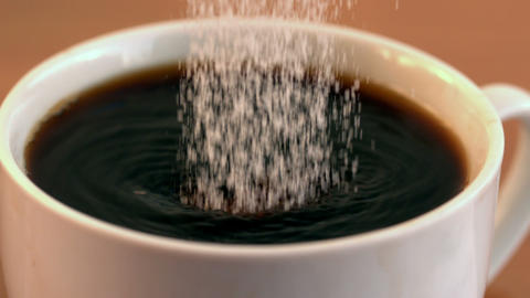 Sugar pouring into cup of coffee Stock Video Footage