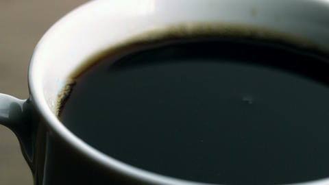 Beans falling into cup of coffee Stock Video Footage