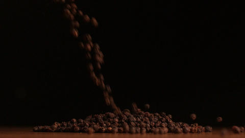 Pepper corns pouring on black background Stock Video Footage
