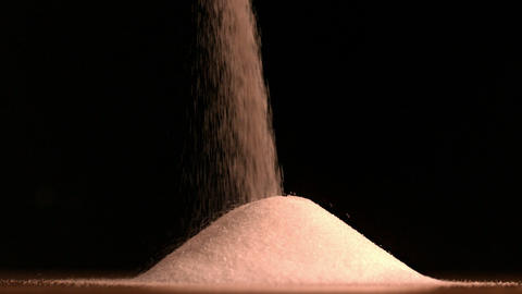 Sugar pouring on black background Footage
