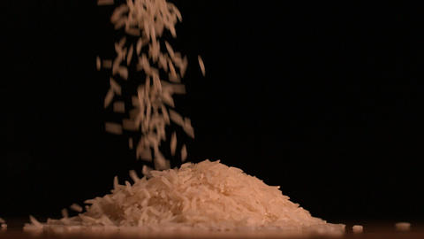 White rice pouring on black background Stock Video Footage