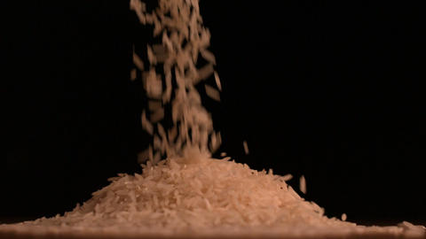 White rice pouring on black background Footage