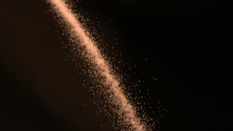 Golden sugar falling against black background Stock Video Footage