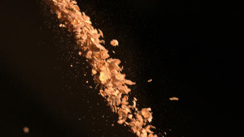Cereal flakes falling against black background Footage