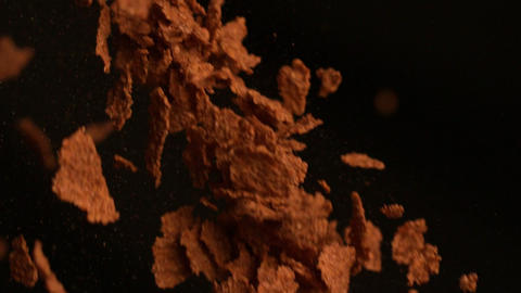 Cereal flakes falling against black background Stock Video Footage
