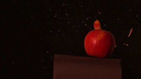 Arrow shooting through red apple on black background Footage