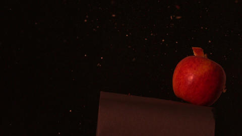 Arrow shooting through red apple on black background Stock Video Footage