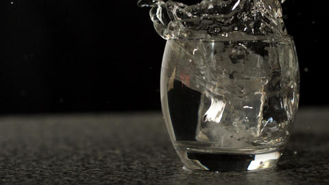 Ice cube falling into glass of water Stock Video Footage