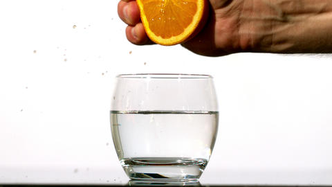 Hand squeezing juice of orange into glass of water Stock Video Footage
