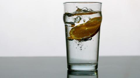 Orange slice falling into pint of water Stock Video Footage