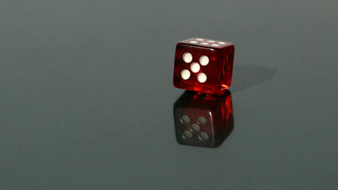 Red dice spinning on reflective surface Stock Video Footage