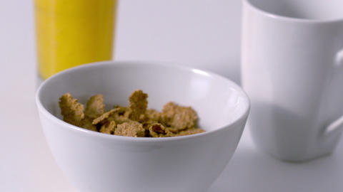 Cereal pouring into a bowl at breakfast table Footage