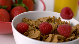 Raspberries pouring into cereal bowl at breakfast table Footage