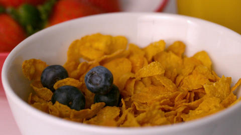 Blueberries pouring into cereal bowl at breakfast table Stock Video Footage