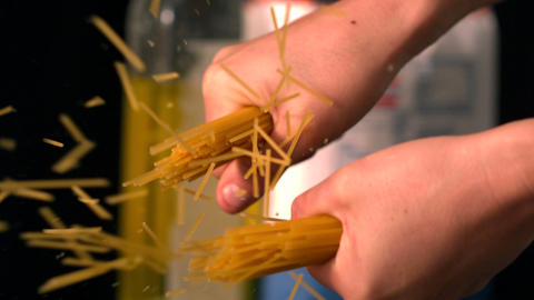 Hands snapping spaghetti in half Stock Video Footage