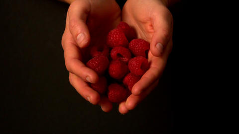 Woman spilling raspberries from her hands Stock Video Footage