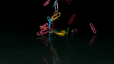 Paperclips falling on black background Stock Video Footage