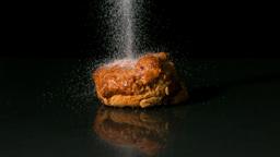 Sugar sprinkling on scone on black background Footage