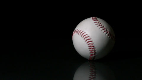 Baseball spinning on black surface Stock Video Footage