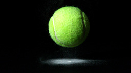 Tennis ball falling on black background Footage