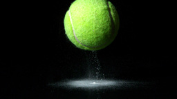 Tennis ball falling on black background Stock Video Footage