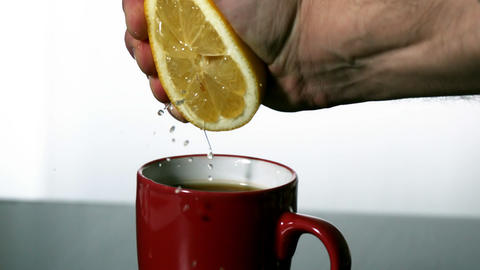 Man squeezing lemon into red mug Stock Video Footage