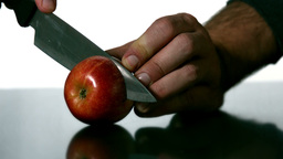 Man slicing apple with large knife Footage