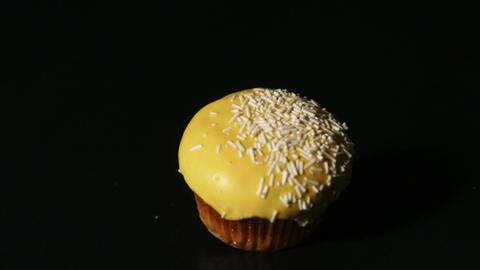 Yellow cupcake falling on black background Footage