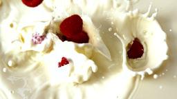 Raspberries falling in glass of milk Footage