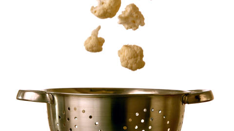 Cauliflower falling into colander on white backgro Footage