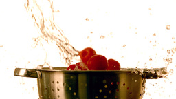 Cherry tomatoes and water falling into colander Footage
