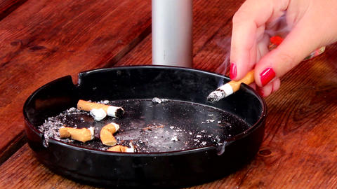 Woman puts smoldering cigarette in ashtray Footage