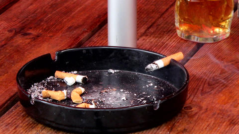 Woman puts smoldering cigarette in ashtray Stock Video Footage