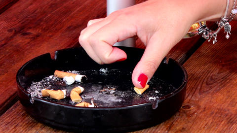 Woman's Hand Extinguish Butt In Ashtray stock footage