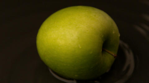 Green apple spinning on wet surface Footage