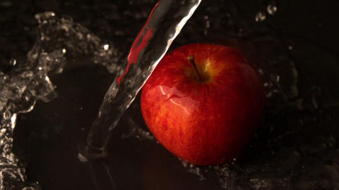 Water pouring over red apple Footage